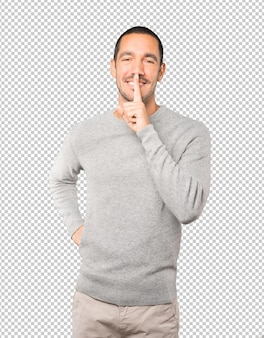 彼の指で身振りで示す沈黙を求める幸せな若い男 Premium Psd