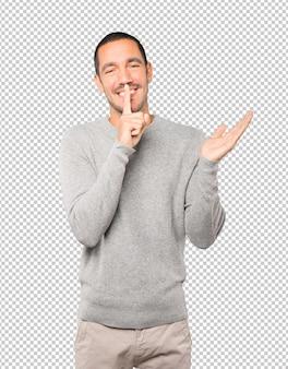 彼の指で身振りで示す沈黙を求める幸せな若い男