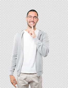 Happy young man asking for silence gesturing with his finger