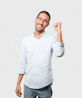 Счастливый молодой человек делает конкурсный жест