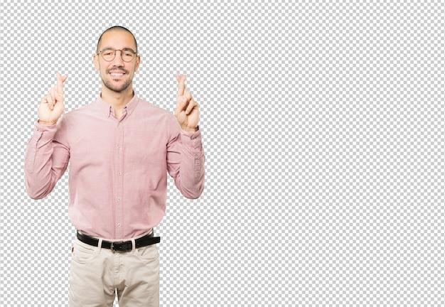 Счастливый молодой человек делает жест скрещенные пальцы