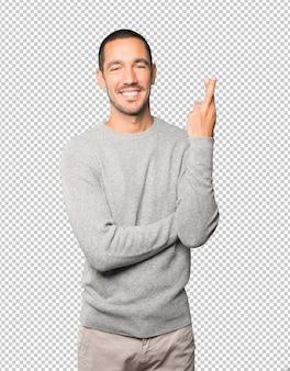 Счастливый молодой человек делает жест скрещенными пальцами