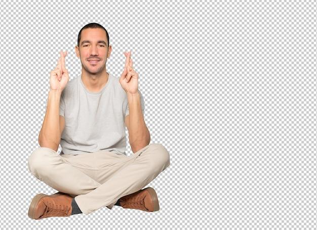 交差した指のジェスチャーをしている幸せな若い男