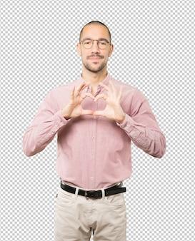 Счастливый молодой человек делает жест любви своими руками
