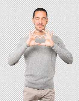 Счастливый молодой человек делает жест любви руками