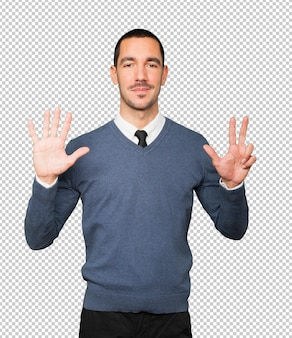 彼の手で8番のジェスチャーをしている幸せな若い男