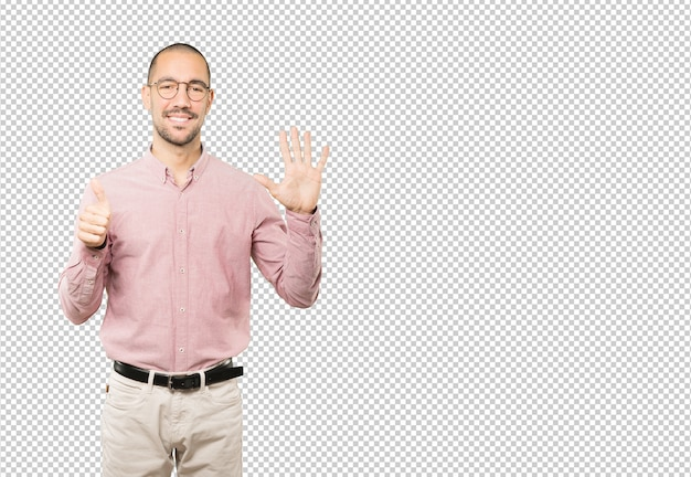 彼の手で数6のジェスチャーをして幸せな若い男
