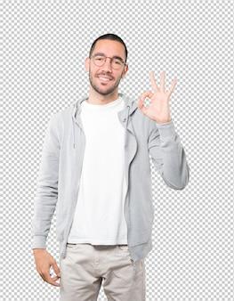 Счастливый молодой человек делает все правильно жест