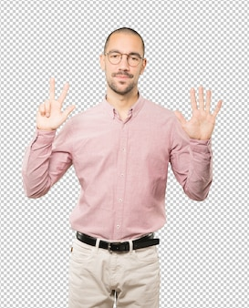 Happy young man doing a number eight gesture with his hands