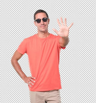 Happy young man doing a number five gesture
