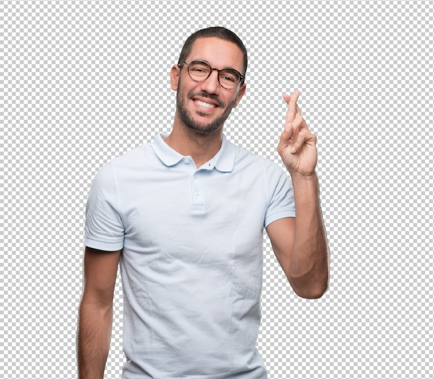 Happy young man doinga gesture of crossed fingers