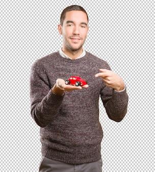 おもちゃの車を持つ幸せな若い男
