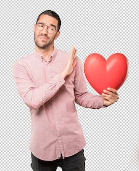 Happy young man holding a big toy heart and doing gestures about valentine's day