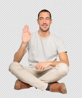 彼の手のひらで停止のジェスチャーをする幸せな若い男