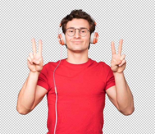 彼の手で勝利のジェスチャーをする幸せな若い男