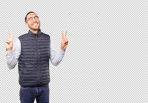 Счастливый молодой человек, делая жест победы пальцами