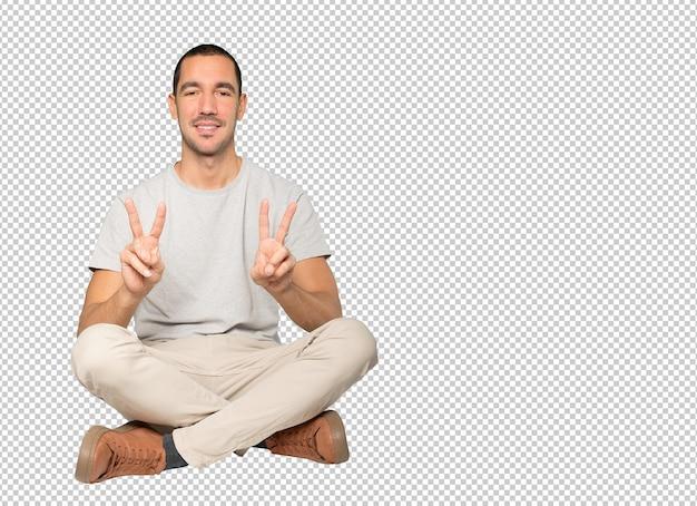 그의 손가락으로 승리 제스처를 만드는 행복 한 젊은 사람 프리미엄 PSD 파일