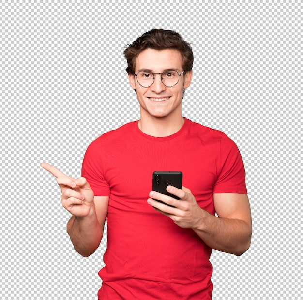 Happy young man pointing up and using a mobile phone