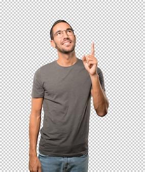 Счастливый молодой человек, указывая пальцем