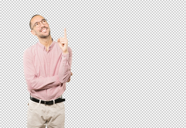 Happy young man pointing up with his finger