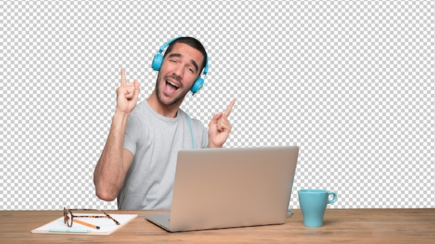Happy young man sitting at his desk and using a headphones