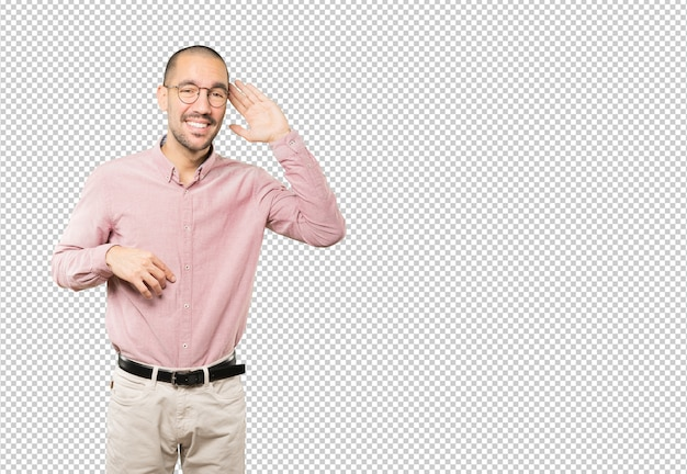 Happy young man smiling and making a gesture of trying to hear something