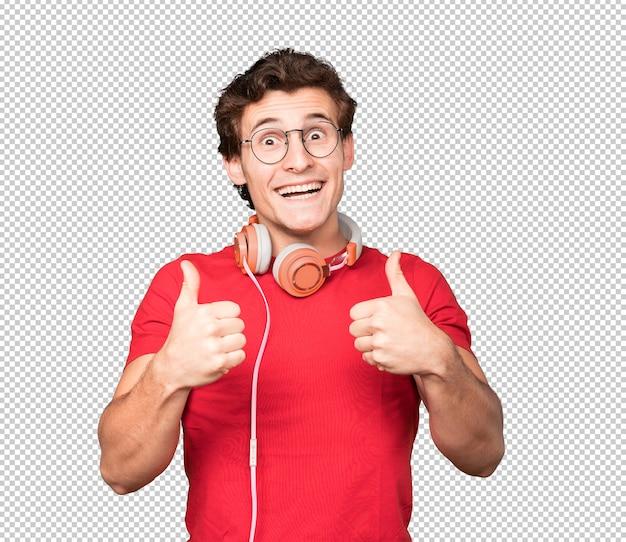 大丈夫なジェスチャーでヘッドフォンとスマートフォンを使用して幸せな若い男