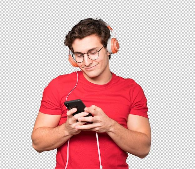 ヘッドフォンとスマートフォンを使用して幸せな若い男