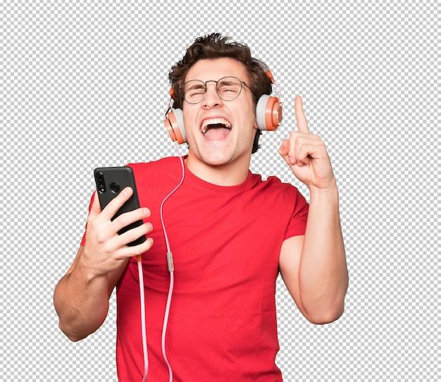 ヘッドフォンとスマートフォンを使用して幸せな若い男 Premium Psd