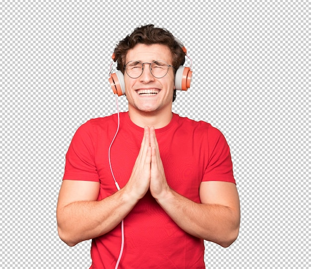 Happy young man using headphones and a smartphone and making a gesture of praying