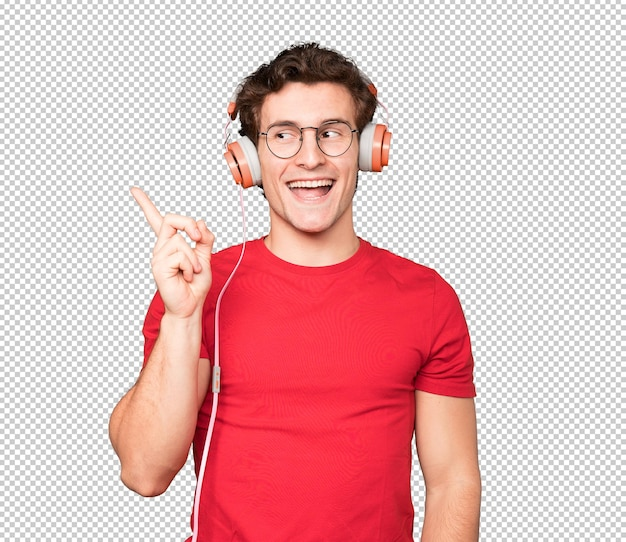 Happy young man using headphones and a smartphone and pointing up