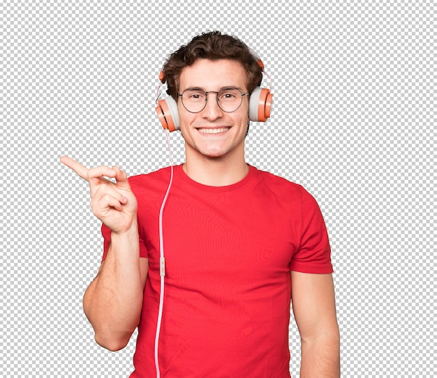 Happy young man using headphones and a smartphone and pointing