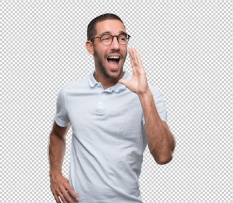 Happy young man using his hand to shout