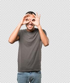 Счастливый молодой человек, используя его руки, как бинокль