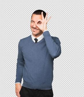 쌍안경처럼 그의 손을 사용하여 행복 한 젊은 남자