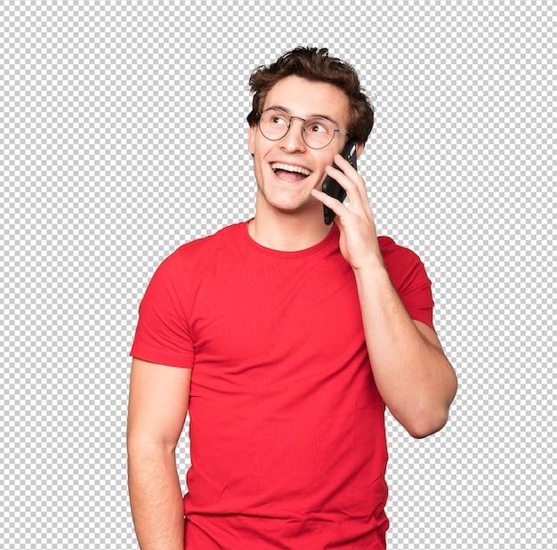 Счастливый молодой человек, используя свой мобильный телефон