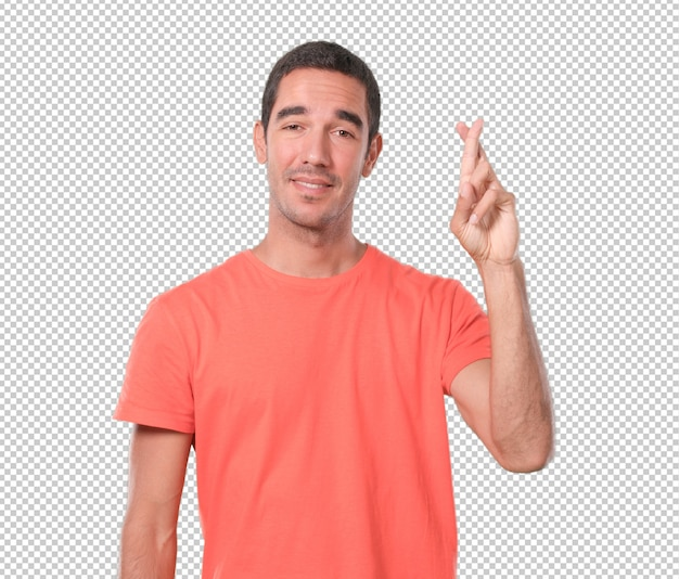 Happy young man with crossed fingers gesture