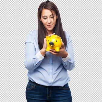 Счастливая молодая женщина с копилкой