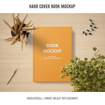Hard cover book mockup with plant and pencils