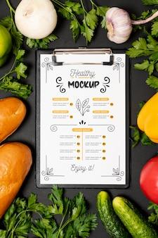 野菜とクリップボードの健康的な朝食