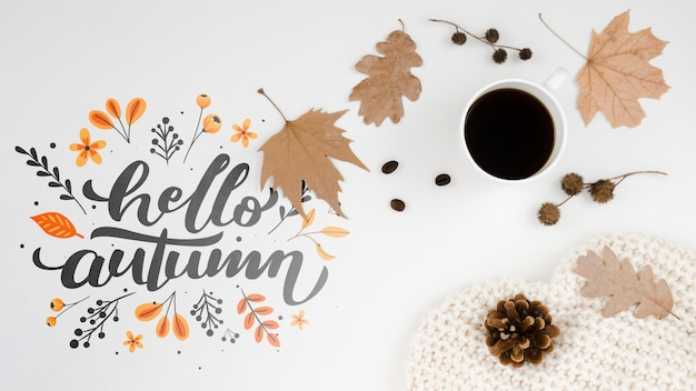 Hello autumn lettering next to cup of coffee