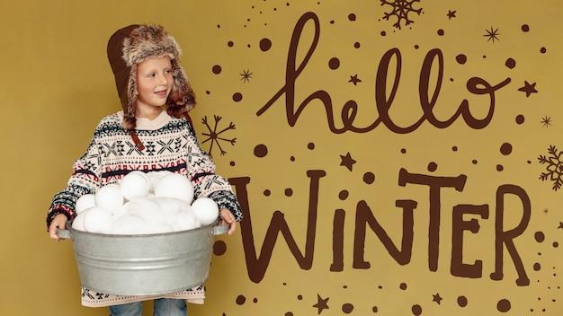 こんにちは、冬のテキストと雪だるまいっぱいのバケツを持つ少年