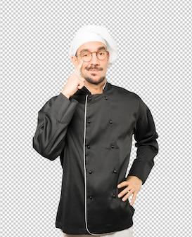 Сомневающийся молодой шеф-повар делает жест осторожности, указывая рукой на глаз