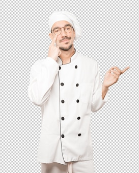 Hesitant young chef making a gesture of being careful with his hand pointing at his eye