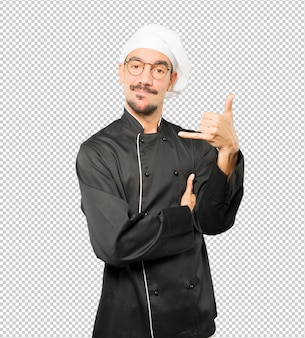 Hesitant young chef making a gesture of calling with the hand