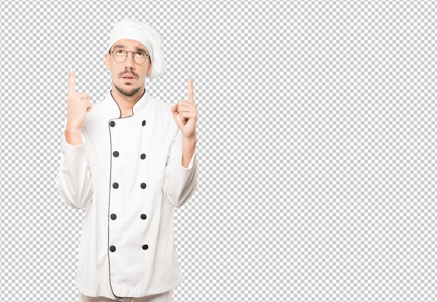 Hesitant young chef pointing up with his finger