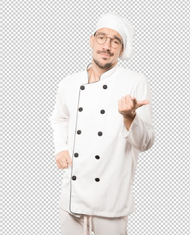 Hesitant young chef pointing at you with his finger