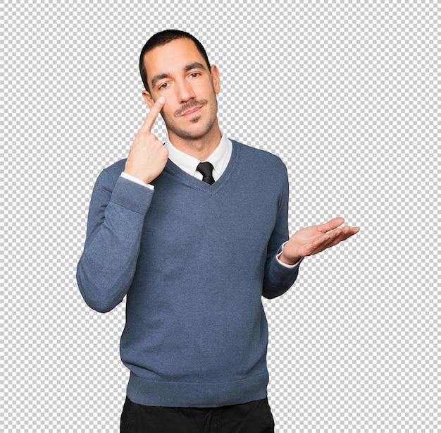 躊躇している青年が手を指さして注意するジェスチャー