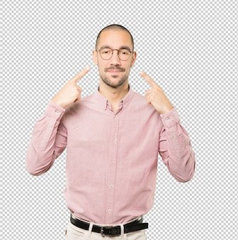 Hesitant young man making a gesture of being careful with his hand pointing at his eye