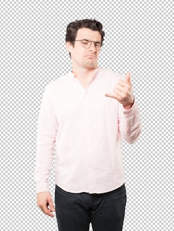 Hesitant young man making a gesture of calling with the hand